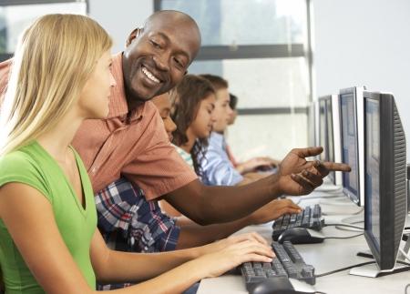 Niños ayudando: Maestro ayudar a los estudiantes que trabajan en los ordenadores en el aula Foto de archivo