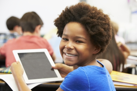 child school: Pupil In Class Using Digital Tablet Stock Photo
