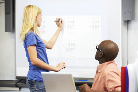 11 year old girl: Female Student Writing Answer On Whiteboard Stock Photo