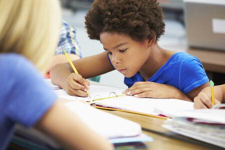 ni�os escribiendo: Los alumnos que estudian en pupitres en el aula Foto de archivo