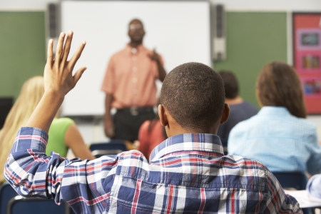Masculino de la pupila que levanta la mano en clase Foto de archivo - 24489720