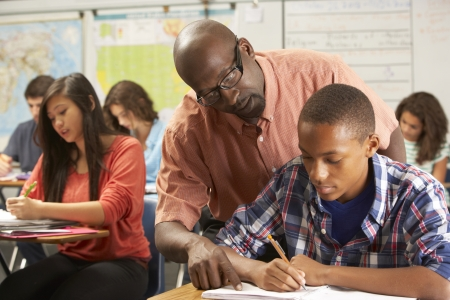 Teacher Helping Male Pupil Studying At Desk In Classroom Stock Photo