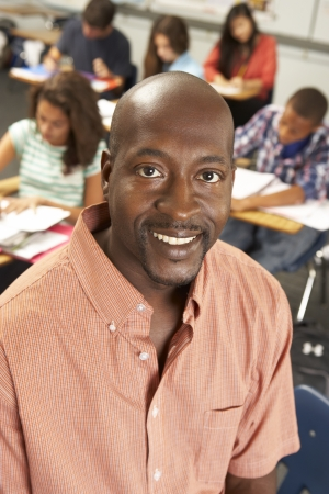 13 year old boy: Portrait Of Teacher In Classroom Stock Photo