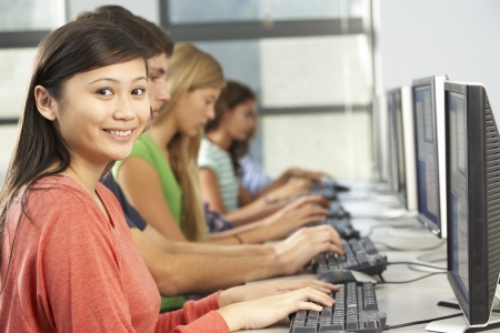 třída: Skupina studentů pracuje na počítačích v učebně