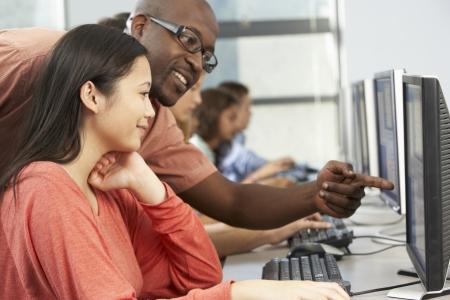 maestra ense�ando: Maestro ayudar a los estudiantes que trabajan en los ordenadores en el aula Foto de archivo