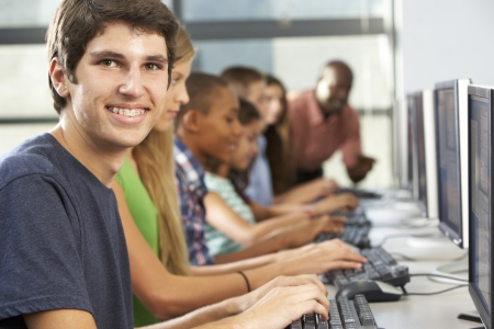 teacher teaching: Group Of Students Working At Computers In Classroom