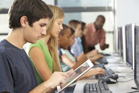 adolescentes estudiando: Muchacho que usa la tableta digital en clase del ordenador Foto de archivo