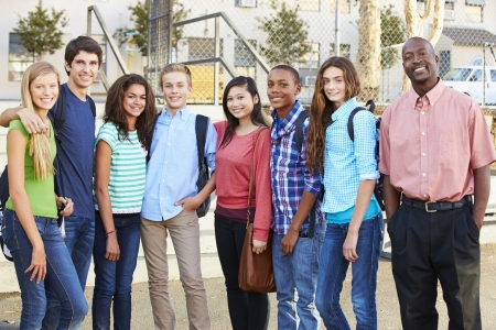 Group Of Teenage Pupils With Teacher Outside Classroom photo
