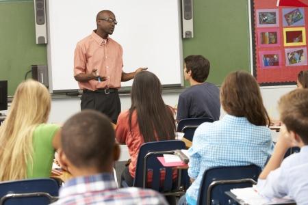 secondary school teacher: Teacher Using Interactive Whiteboard During Lesson Stock Photo