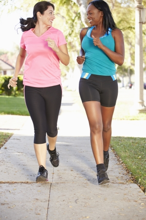 Two Female Runners Exercising On Suburban Street photo