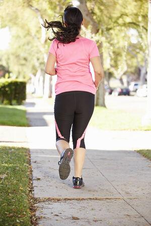 suburban street: Rear View Of Female Runner Exercising On Suburban Street Stock Photo