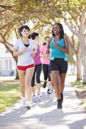 asian american: Group Of Female Runners Exercising On Suburban Street Stock Photo