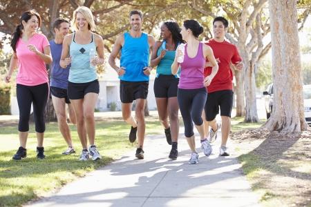 hacer footing: Grupo de corredores en la calle suburbana