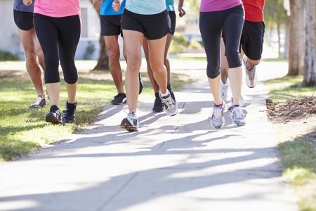 gens courir: Gros plan des pieds des coureurs sur rue suburbaine