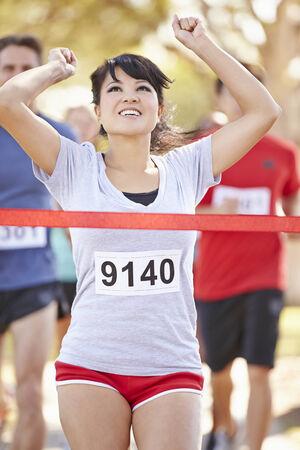 finishing line: Female Runner Winning Marathon Stock Photo