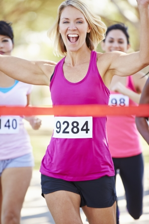 Female Runner Winning Marathon Stock Photo