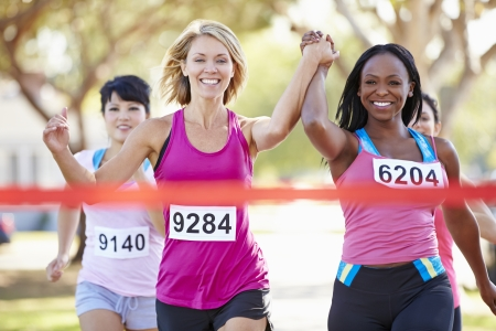 atletisch: Twee Vrouwelijke Runners Finishing Race Samen Stockfoto