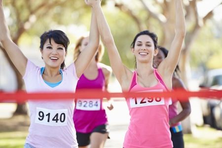 caucasian race: Two Female Runners Finishing Race Together Stock Photo