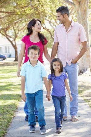 郊外の通りに沿って歩いて家族 写真素材