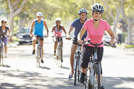 bike riding: Group Of Cyclists On Suburban Street Stock Photo