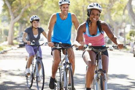bike riding: Group Of Cyclists On Suburban Street Stock Photo