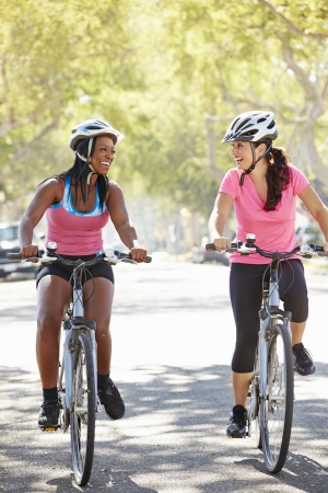 Two Women Cycling On Suburban Street photo