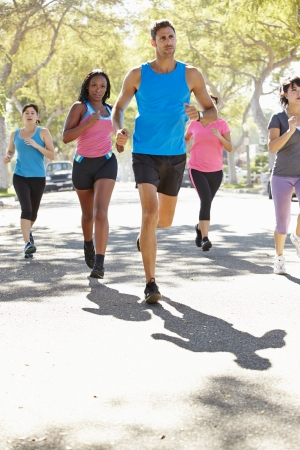 Group Of Women Running Along Street With Personal Trainer photo