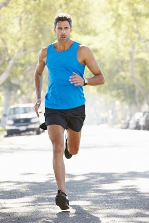 coureur: Homme Runner s'exer�ant sur rue suburbaine
