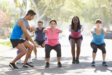 woman fitness: Groupe de personnes exer�ant la rue avec un entra�neur personnel