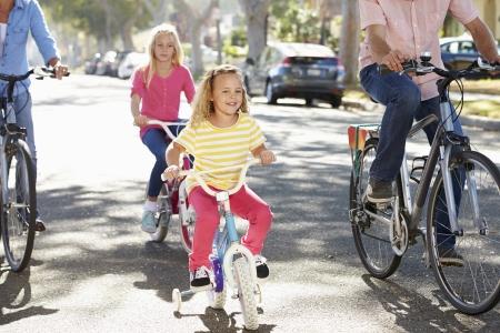 suburban street: Family Cycling On Suburban Street