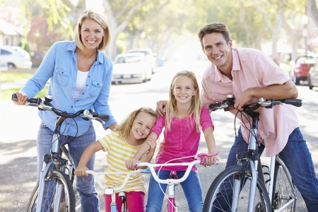 suburban: Family Cycling On Suburban Street