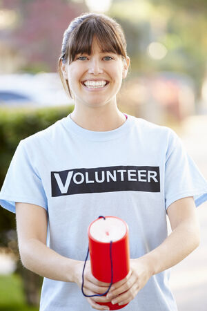charity collection: Portrait Of Charity Volunteer On Street With Collection Tin