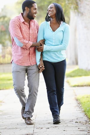 Couple Walking Along Suburban Street Together photo