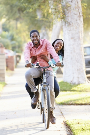 Couple Cycling Along Suburban Street Together photo