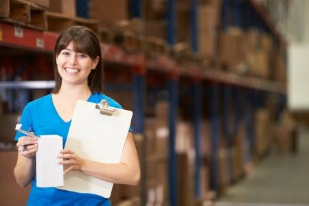 Vrouwelijke Arbeider In Uitkering Warehouse Stockfoto