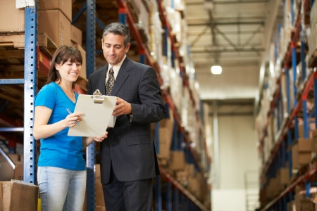 loading bay: Businessman And Female Worker In Distribution Warehouse Stock Photo