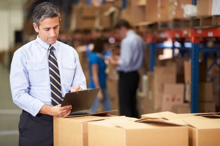 small business: Manager In Warehouse Checking Boxes