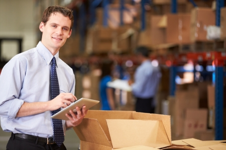 order shipment: Manager In Warehouse Checking Boxes Using Digital Tablet Stock Photo