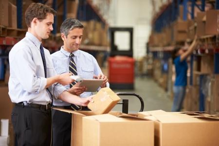 Los hombres de negocios de cheques Cajas Con la tableta digital y el escáner Foto de archivo - 24490204