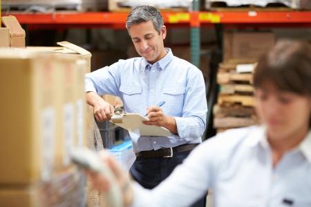 barcode scanning: Manager In Warehouse With Worker Scanning Box In Foreground Stock Photo
