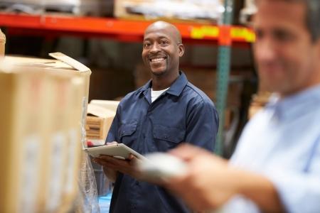 ouvrier: Gestionnaire dans l'entrepôt avec la boîte de numérisation travailleurs au premier plan