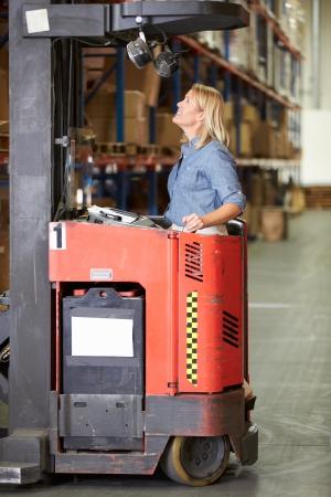 fork lift: Woman Driving Tenedor Lift Truck En Almac�n Foto de archivo
