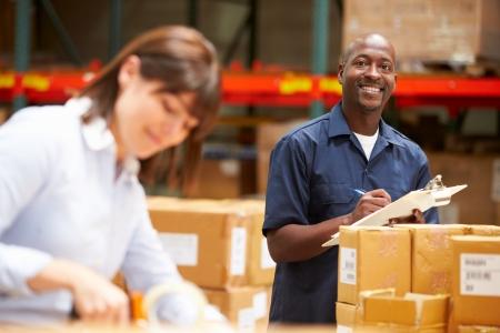 ouvrier: Travailleurs dans l'entrepôt préparation des marchandises pour l'expédition