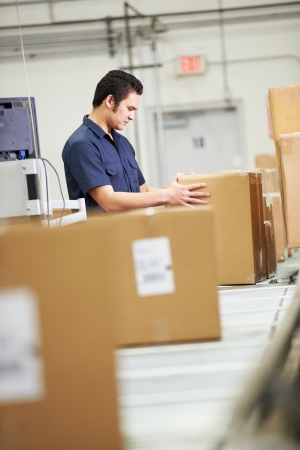 Worker Checking Goods On Belt In Distribution Warehouse photo