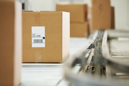 factory line: Goods On Conveyor Belt In Distribution Warehouse Stock Photo
