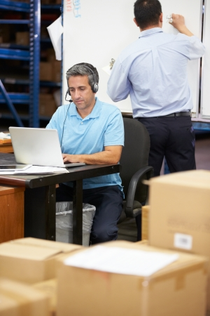 Worker In Warehouse Wearing Headset And Using Laptop photo