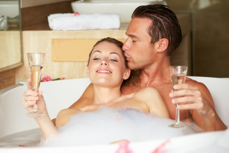 bubble bath: Couple Relaxing In Bath Drinking Champagne Together Stock Photo