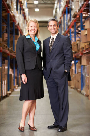 Businesswoman And Businessman In Distribution Warehouse photo