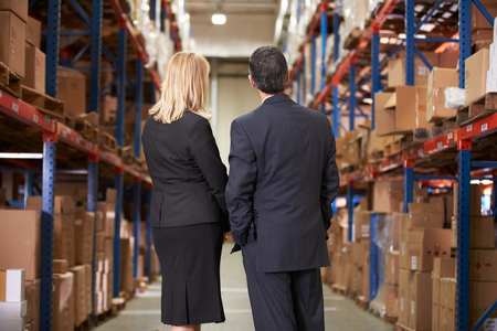 loading bay: Rear View Of Businesswoman And Businessman In Warehouse