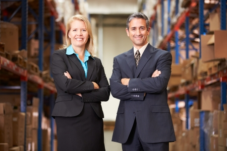small business: Businesswoman And Businessman In Distribution Warehouse Stock Photo